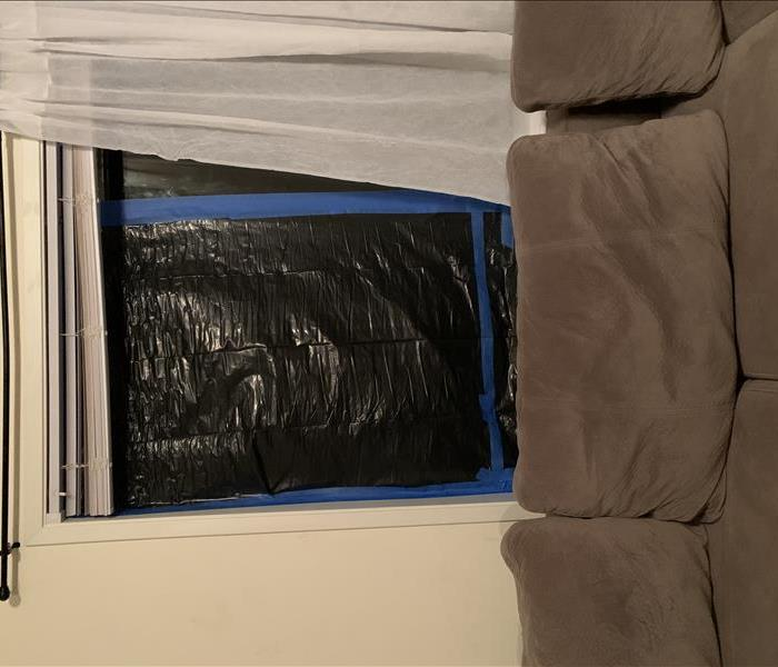 Clean couch and taped up window with garbage bag