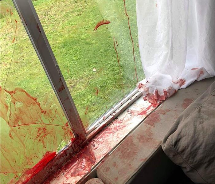 Broken glass window, blood on couch