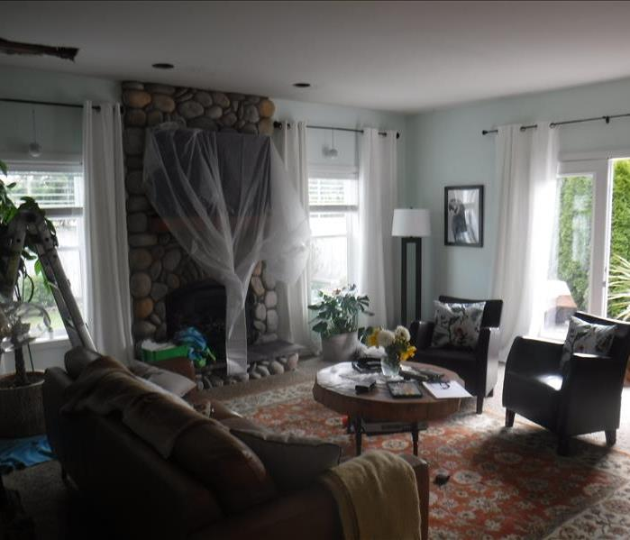 Room with furniture, windows, fireplace tarped off