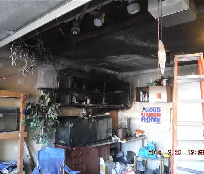 Black walls, ceiling, and cabinet from fire and smoke in a garage.