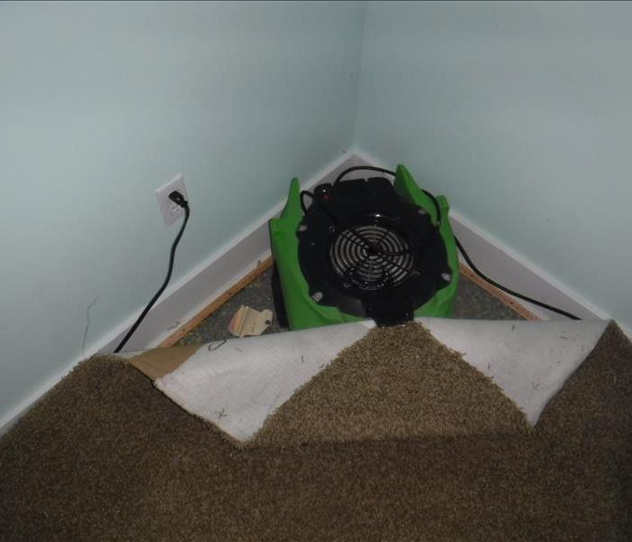 Fan in a corner with a piece of green equipment